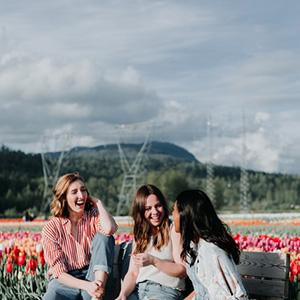 Jeunes filles qui parlent et rient dans un champ de tulipes