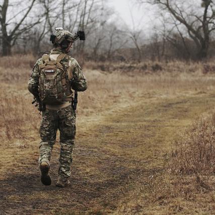 jeune militaire en tenue de camouflage qui marche dans la forêt