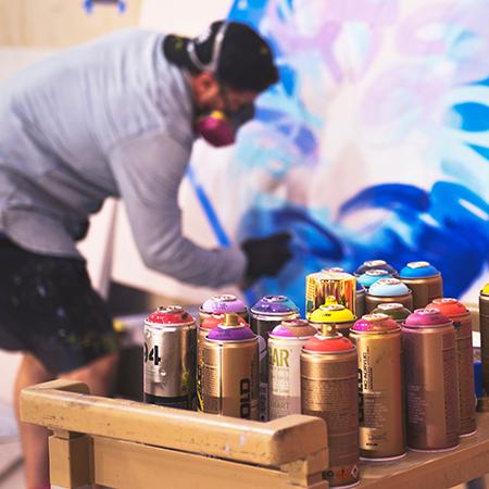 Jeune qui peint un mur à la bombe