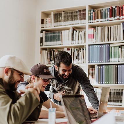 groupe de jeunes riant devant un ordinateur dans une salle d'études