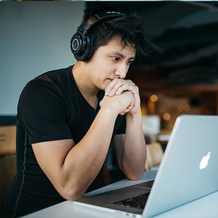 jeune regardant un ordinateur un casque sur les oreilles