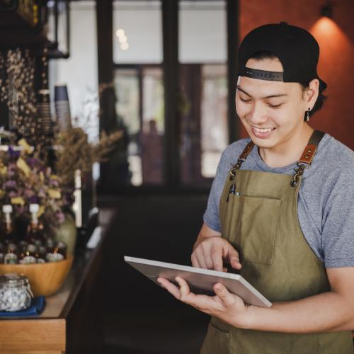 jeune barman asiatique tenant une tablette pour prendre les commandes dans un café